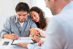 Young attractive couple signing contract Stock Photos