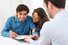 Young attractive couple signing contract Royalty Free Stock Photo