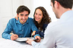Young attractive couple signing contract Royalty Free Stock Photos