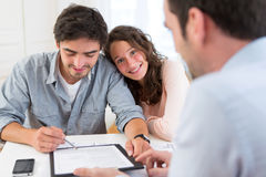 Young attractive couple signing contract Stock Photography