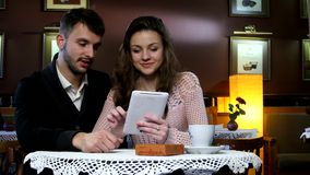Young attractive couple sitting in a cafe and stock video footage