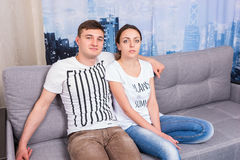 Young attractive couple sitting on a couch together Stock Images