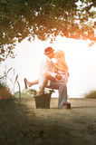 Young attractive couple sitting flirting together on dirt road Stock Photos