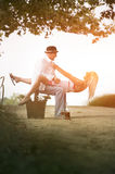 Young attractive couple sitting flirting together on dirt road Royalty Free Stock Photo