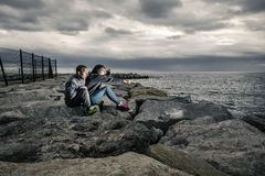 Young and attractive couple is sitting on the pier made of stones. Young and attractive couple is sitting on the pier on cloudy summer`s day and they are Royalty Free Stock Photo