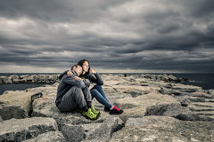 Young and attractive couple is sitting on the pier made of stones. Young and attractive couple is sitting on the pier on cloudy summer`s day and they are Stock Photography