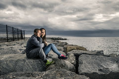 Young and attractive couple is sitting on the pier made of stones. Young and attractive couple is sitting on the pier on cloudy summer`s day and they are Stock Image