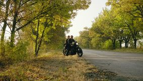 Young attractive couple starting to ride a motorcycle, traveling together on the asphalt road on a sunny day in forest. In autumn stock video footage