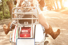 Young attractive couple traveling on scooter along dirt road. Close view of young attractive couple traveling on scooter along dirt road Royalty Free Stock Images