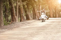 Young attractive couple traveling on scooter along dirt road Stock Photos