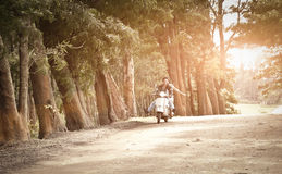 Young attractive couple traveling on scooter along dirt road. Through trees Stock Photo