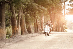 Young attractive couple traveling on scooter along dirt road. Through trees Royalty Free Stock Images