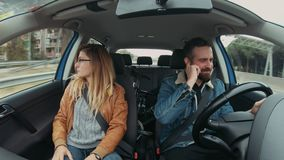 Cute hipster couple drives car at roadtrip. Young attractive couple or two friends ride in small hybrid car, have argument about personal issues, shout and argue stock video footage