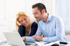Young attractive couple using laptop at home Stock Image