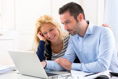 Young attractive couple using laptop at home Stock Photo