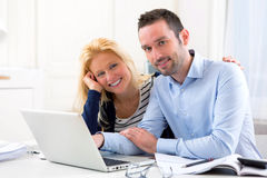 Young attractive couple using laptop at home Royalty Free Stock Photo