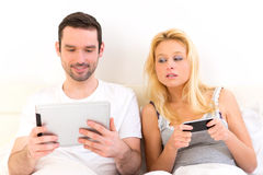 Young attractive couple using mobile and tablet in bed Stock Images