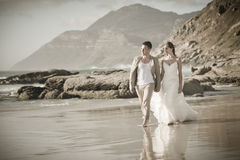 Young attractive couple walking along beach wearing white Royalty Free Stock Photo
