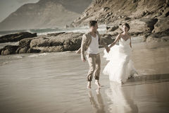 Young attractive couple walking along beach wearing white Stock Images