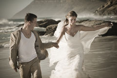 Young attractive couple walking along beach wearing white Stock Photography