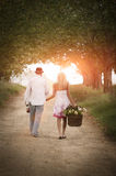 Young attractive couple walking along dirt road at sunrise Royalty Free Stock Photography
