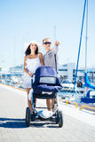 Young and attractive couple walking with a baby pram Royalty Free Stock Images