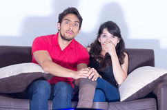 Young attractive couple watching movie at home Royalty Free Stock Images