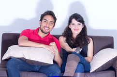 Young attractive couple watching movie at home Royalty Free Stock Photos