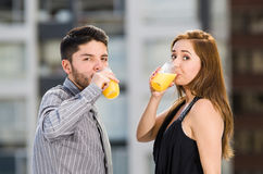 Young attractive couple wearing formal clothes standing on rooftop drinking from glass with yellow drink, posing for Stock Photography