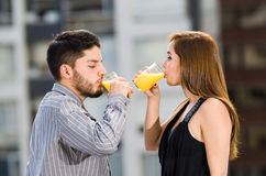 Young attractive couple wearing formal clothes standing on rooftop facing each other drinking from glass with yellow Stock Photography