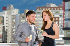 Young attractive couple wearing formal clothes standing on rooftop holding cocktails and interacting, city buildings Stock Images