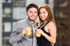 Young attractive couple wearing formal clothes standing on rooftop holding glass with yellow drink, posing, smiling and Stock Images