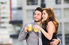 Young attractive couple wearing formal clothes standing on rooftop holding glass with yellow drink, posing, smiling and Royalty Free Stock Photo