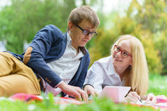 Young attractive couple wearing glasses is working or studying with laptop book note and pen lying on blanket in green Royalty Free Stock Images