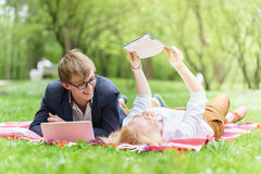 Young attractive couple wearing glasses is working or studying with laptop book note and pen lying on blanket in green park at sun Royalty Free Stock Images
