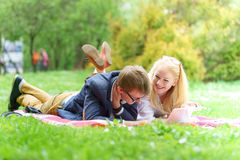 Young attractive couple wearing glasses is working or studying with laptop book note and pen lying on blanket in green park at sun Stock Image