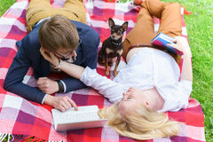 Young attractive couple wearing glasses is working or studying with laptop book note and pen lying on blanket in green park at sun Stock Photography