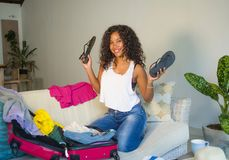 Young attractive and crazy happy black Afro American woman preparing clothes packing stuff in suitcase leaving for holidays trip h royalty free stock image