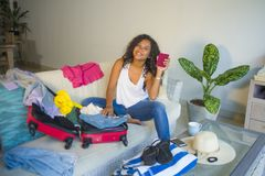 Young attractive and crazy happy hispanic woman preparing clothes packing stuff all messy in suitcase leaving for holidays trip ho royalty free stock photo
