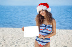 Young, attractive, curly girl in a bathing suit and hat of Santa Claus on the beach holding a white sheet of paper. Stock Photos