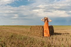 A young attractive curly rural woman in a retro vintage dress and a hat stretching stands near a stack of harvested wheat straw in royalty free stock image