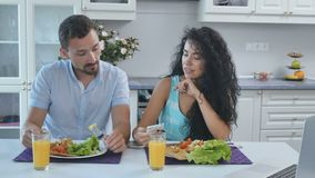 The man annoyed from using smartphone by his wife during breakfast. Young attractive curly woman and handsome man sit at the table. Young people eat their stock video footage