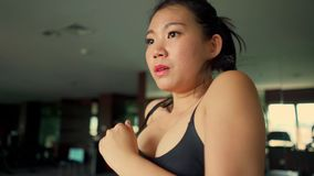 Young attractive and cute Asian Korean woman doing running workout at hotel gym or fitness club jogging in treadmill training hard. In healthy lifestyle and stock video