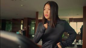 Young attractive and cute Asian Korean woman doing running workout at hotel gym or fitness club jogging in treadmill training hard. In healthy lifestyle and stock footage
