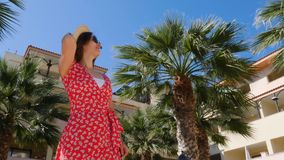 Young attractive cute posing wearing red dress and sunglasses with blue sky and palm trees on the background. Slow motion.  stock footage