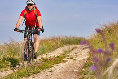 Young attractive cyclist rides on the road in the field in summer season.