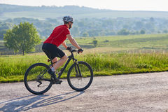 Young attractive cyclist riding mountain bike on the country road. Stock Images