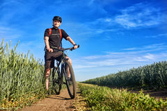 Young attractive cyclist standing up with mountain bicyclist in the summer green field. Royalty Free Stock Photo