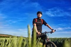 Young attractive cyclist standing up with mountain bicyclist in the summer green field. Royalty Free Stock Photography