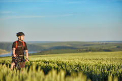 Young attractive cyclist standing up with mountain bicyclist in the summer green field. Stock Photos